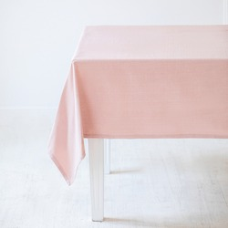A light pink decorative tablecloth on a table on a white background