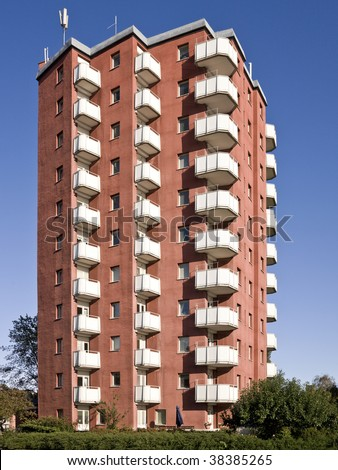 A light red apartment complex against a blue sky