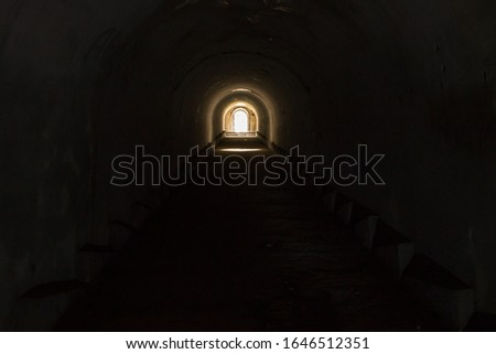 A lighted door leading to freedom from a gloomy dark underground passage at Pospelov Fort in Vladivostok. ストックフォト ©