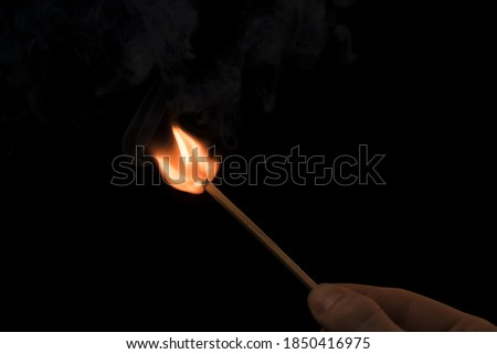 A lighted match on a black background. Hold a lighted match. The fire from the match illuminates everything around. Arson, danger, flash. Macro fire burning on matchstick. Idea, concept, Stock photo ©