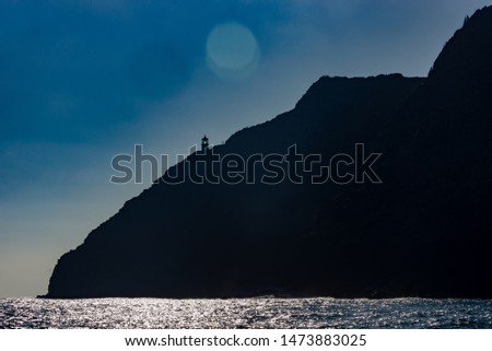 A lighthouse in the distance on the edge of a mountain side with clear blue skies and glistening ocean.