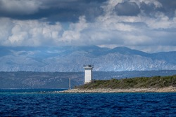 A lighthouse isolated on the Hvar island on the background of hills under a cloudy sky