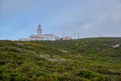 A lighthouse on a green hill in a fog against a blue sky. Cape Rock. Portugal