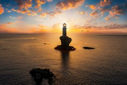 A lighthouse on a steep rock within the calm, mediterranean sea of Greece during summer sunrise, Andros island, Cyclades