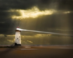 a lighthouse on the welsh coast with light beam and stormy, threatening sky beyond