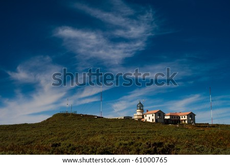 A lighthouse, some houses and a blue sky with some clouds