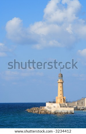A lighthouse with large sky area and some clouds. This lighthouse is in Alexandria, Egypt