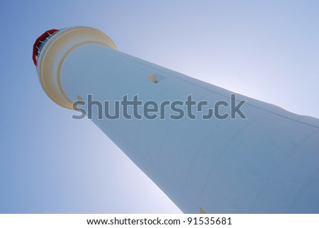 A lighthouse with sun behind - stock photo