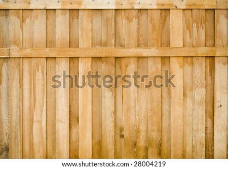 A lightly stained wooden fence with cross bar