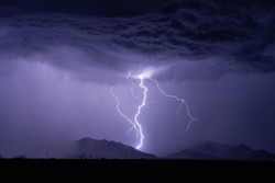 A lightning bolt strikes a mountain during a thunderstorm