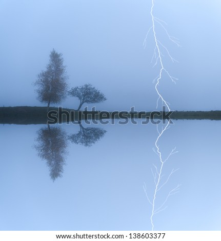A lightning strike behind a pair of trees on a  cool foggy morning, Stowe, Vermont, USA