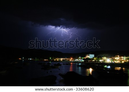 A lightning strike from a late night storm at the sea