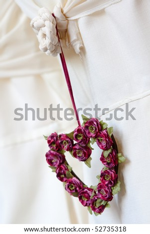A lilac heart-shaped flower decoration at a wedding, hanging from a chair-back