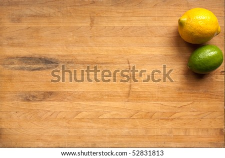 A lime and a lemon sit on a worn butcher block cutting board