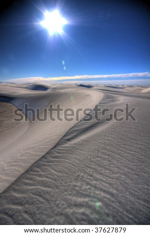 a line in the sand against bright blue sky and flaring sun
