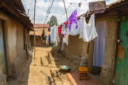 A line of clean clothes dry among the dirty mud and clay homes of the Kibera slum in Nairobi.