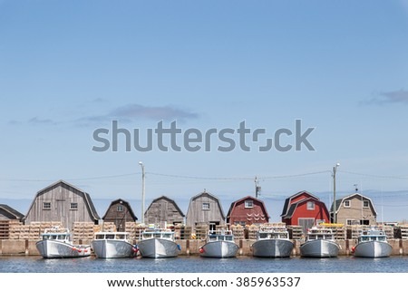A line of fishing sheds and tied up fishing boats at Malpeque Harbour in Prince Edward Island (PEI) on the east coast of Canada. They sky is light blue and there are a few scattered clouds.