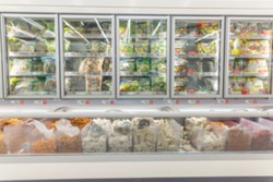 A line of frozen vegetables in the refridgerated goods area at the suprmarket. Front view. Blurred.