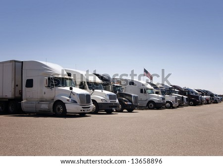 A line of heavy duty freight trucks parked in a row at an American highway truck stop