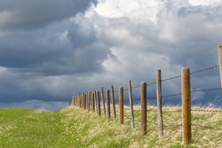 A line of posts and barbwire fence, fade into the distant storm clouds, made up of old posts and new posts