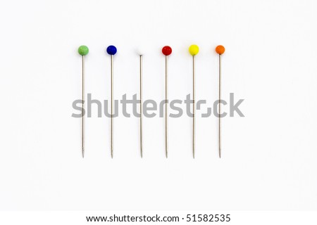 a line of sewing pins on a white background