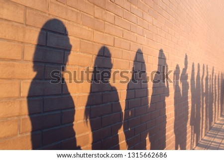 a line of shadows of people lined up against a red brick wall. Stand in a queue to the changes #1315662686