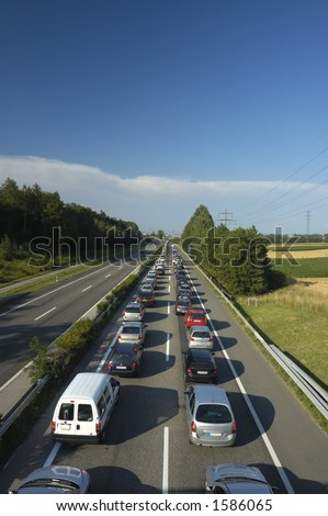 A line of stationary traffic stretches away into the distance on one side of the freeway (motorway, autoroute, autobahn) whilst, in the other direction it is completely clear.