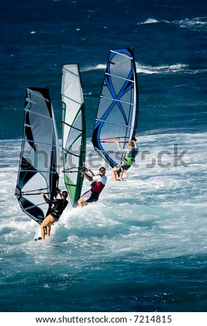 A line of three windsurfers off the coast of Maui