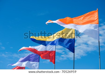 a line of triangle two-colour flags flying against blue sky
