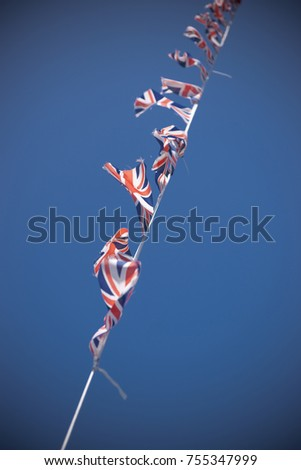 A line of Union Flag (Union Jack) bunting blowing in the wind against a blue sky. #755347999