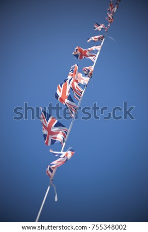 A line of Union Flag (Union Jack) bunting blowing in the wind against a blue sky. #755348002