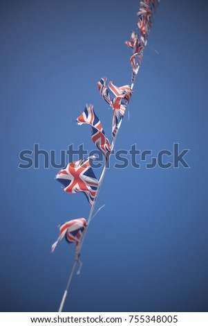 A line of Union Flag (Union Jack) bunting blowing in the wind against a blue sky. #755348005