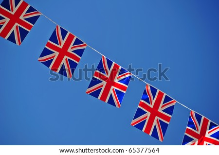 A line of Union Jack flags, stretched across a clear blue sky. Space for text either side of the flags