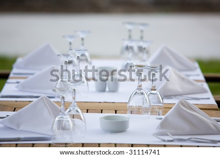 a line of wine glasses fading off in the distance, shallow depth of field. - stock photo