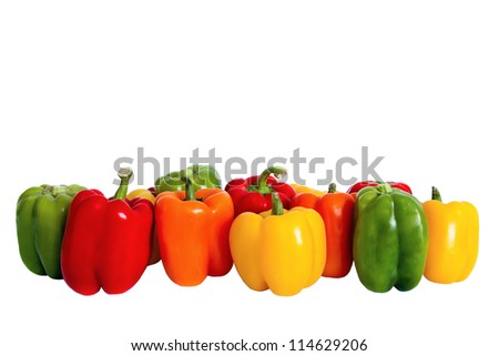 A line-up of bright red, green, orange and yellow peppers is against a white background.