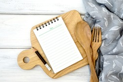 a  lined book notepad paper on chopping cutting board and tablecloth with wooden fork and spoon on white table , recipes food  for healthy habits shot note background concept