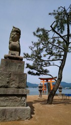 A Lion Guardian statue and a tree in the front. In the background a red japanese gate, day light and blue sky.