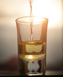 A liquid whiskey alcohol pouring in the shot  with sunset sky background.