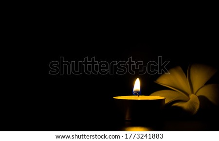 Photo of  A Lit candle and a frangipani flower with empty space for copy text . Aroma candle beside with white flower in the dark makes romantic ambience in the spa room. Sadness, Memorial or Spa background.