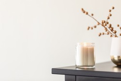 a lit candle on the corner of the dresser next to a gold plated decoration against a cream color wall. modern interior of a bedroom, aroma therapy candle