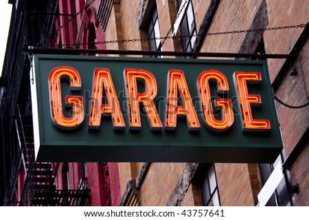 A lit garage neon sign in an urban setting.