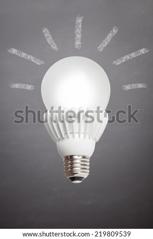 A lit LED bulb is set against a slate background with idea rays coming form the bulb