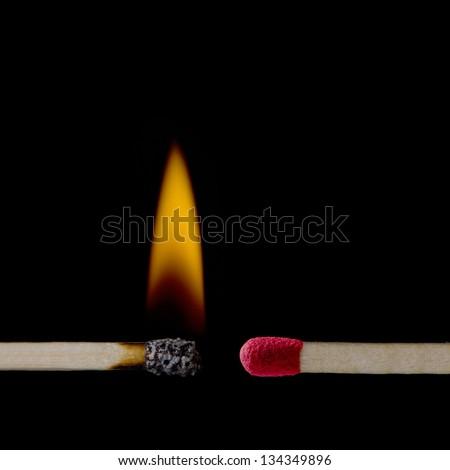 A lit matchstick close to an unlit matchstick