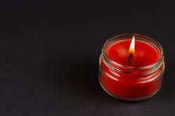 A lit red candle in a glass jar on a black background. The flame of a wax candle in semi-darkness. Side view. Copy space.