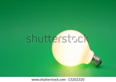 A lit up light bulb on a green background.