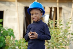 A little African girl acting the role of a construction engineer and architect with a safety helmet on her head, a pen in her hand, and a smartphone in her hand on a construction site