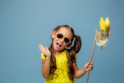 a little Asian girl with long hair holds a windmill toy smiling Studio on a blue background
