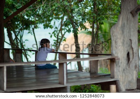 A little asian girl (5 years old) sitting alone on a wooden balcony and expressing facial expressions are disappointed with garden background. Emotional Perception of Children concept. #1252848073