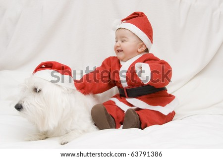 A little baby an his puppy dressed like a Santa Claus.