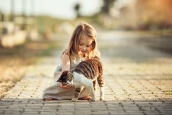 A little barefooted girl in a gray linen dress is stroking a cat. Sunny summer evening in the village. Countryside background. Image with selective focus, toning and noise effects.